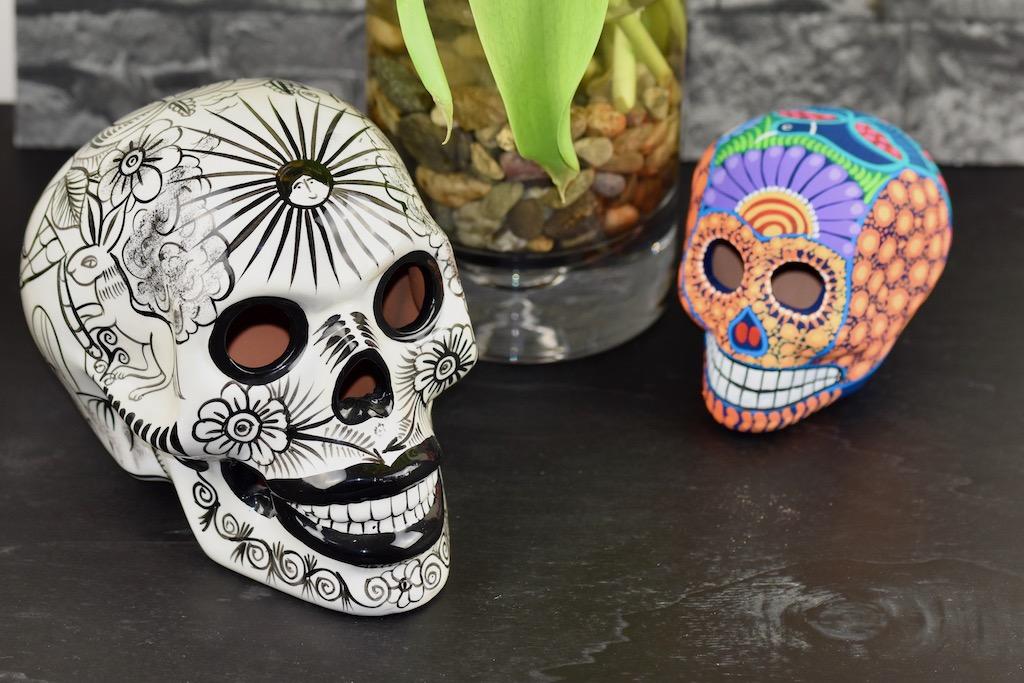 2 Totenköpfe und Blumenvase, schwarzer Untergrund, grauer Hintergrund